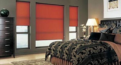 Red roller shades in a guest bedroom